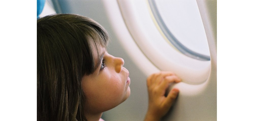 A young girl looks out the passenger window of an Airbus commercial aircraft.