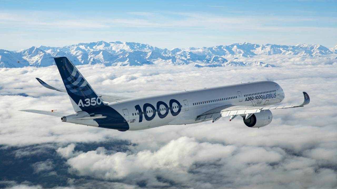 Side view of an Airbus A350-1000 widebody aircraft flying above the clouds with mountains in the background