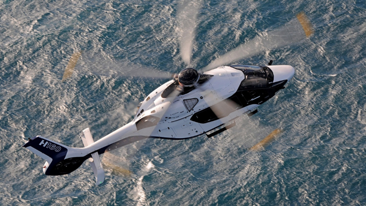 Aerial view of an Airbus H160 helicopter flying over water