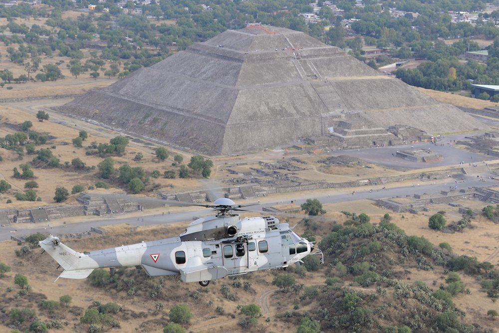 An Airbus H225M military helicopter in service with the Mexican Air Force flies near one of Mexico's pyramids.