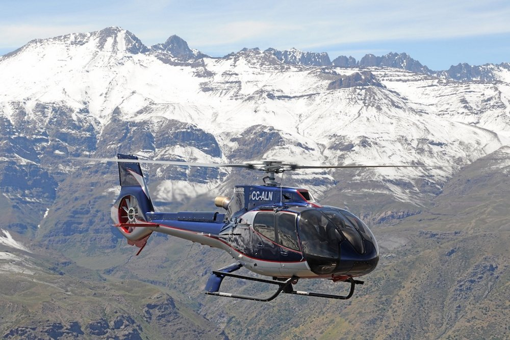 An Airbus H130 helicopter flies near mountainous terrain in Chile.