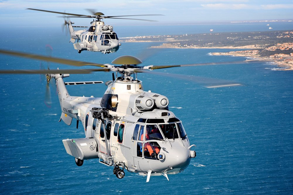 Two Airbus H225M Super Puma helicopters delivered to the Royal Thai Air Force fly in formation over a coastal setting.