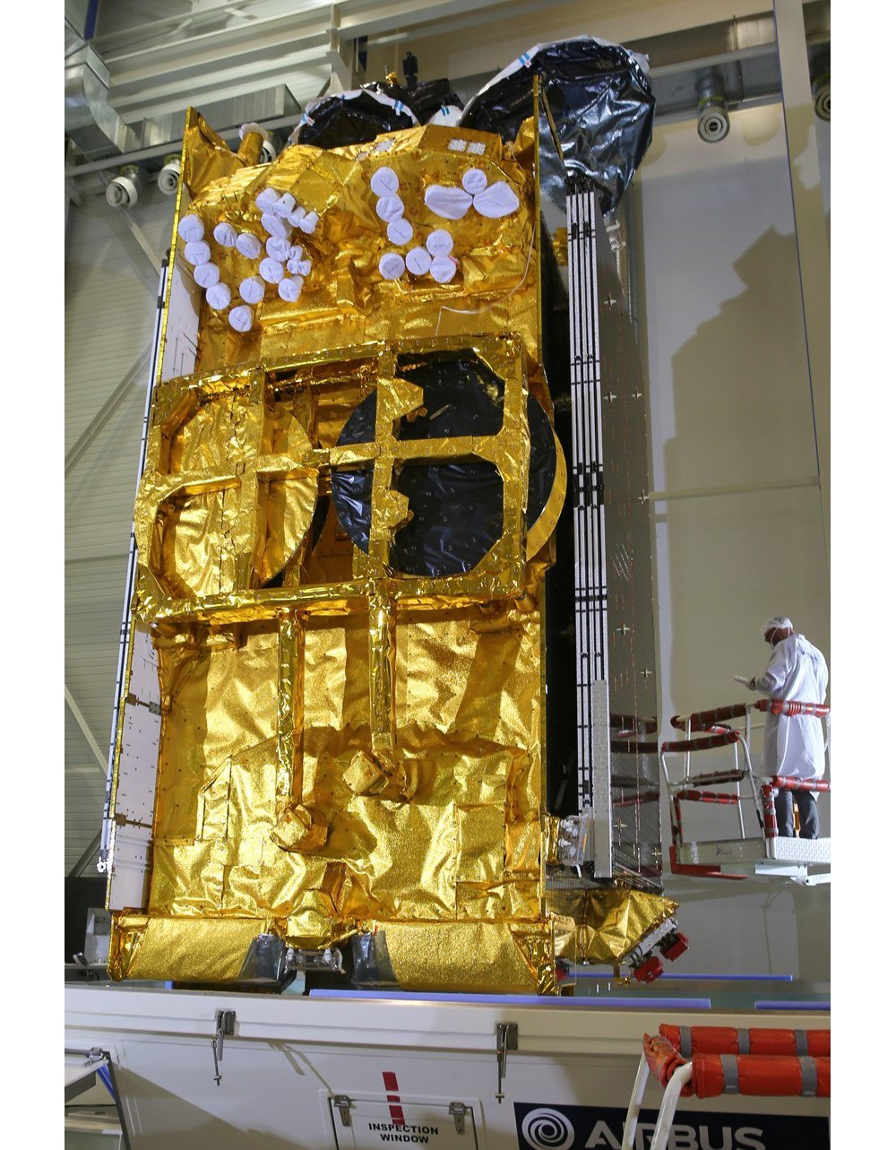 The Airbus-produced SKY Brasil-1 telecommunications satellite is evaluated in a clean room setting.