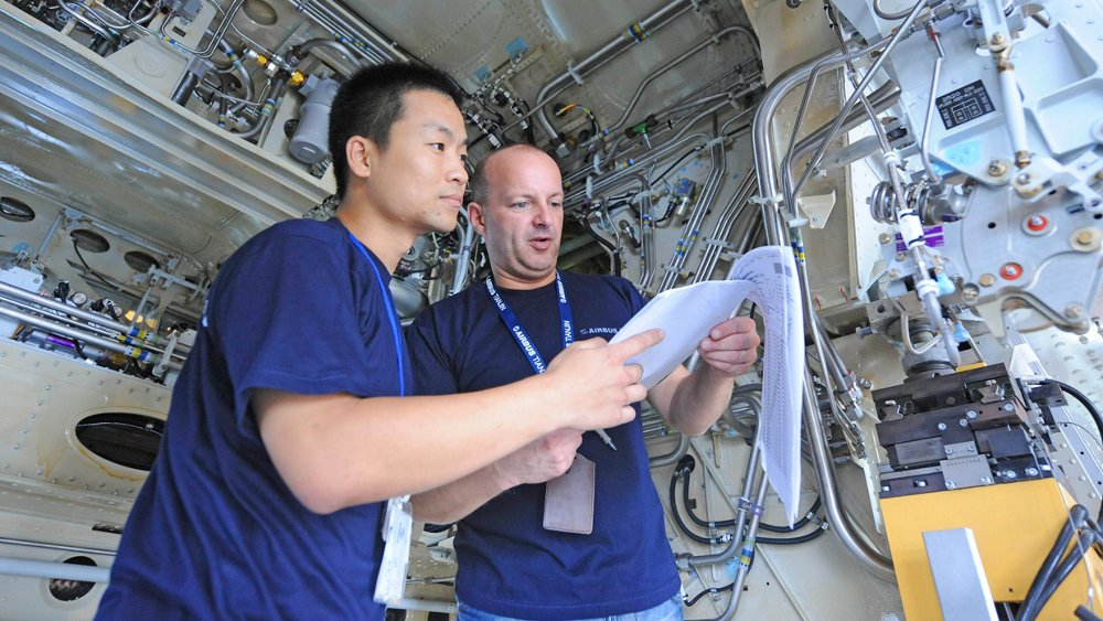 Two Airbus employees review documentation at the company's final assembly line in Tianjin, China.