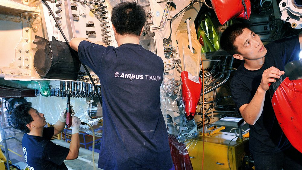 Three Airbus employees are shown working at the company's final assembly line in Tianjin, China.