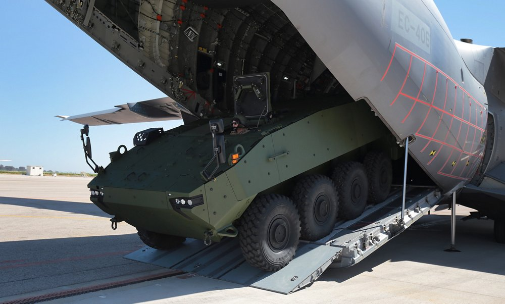 A heavy infantry fighting vehicle is rolled out from an A400M military airlifter's cargo hold.