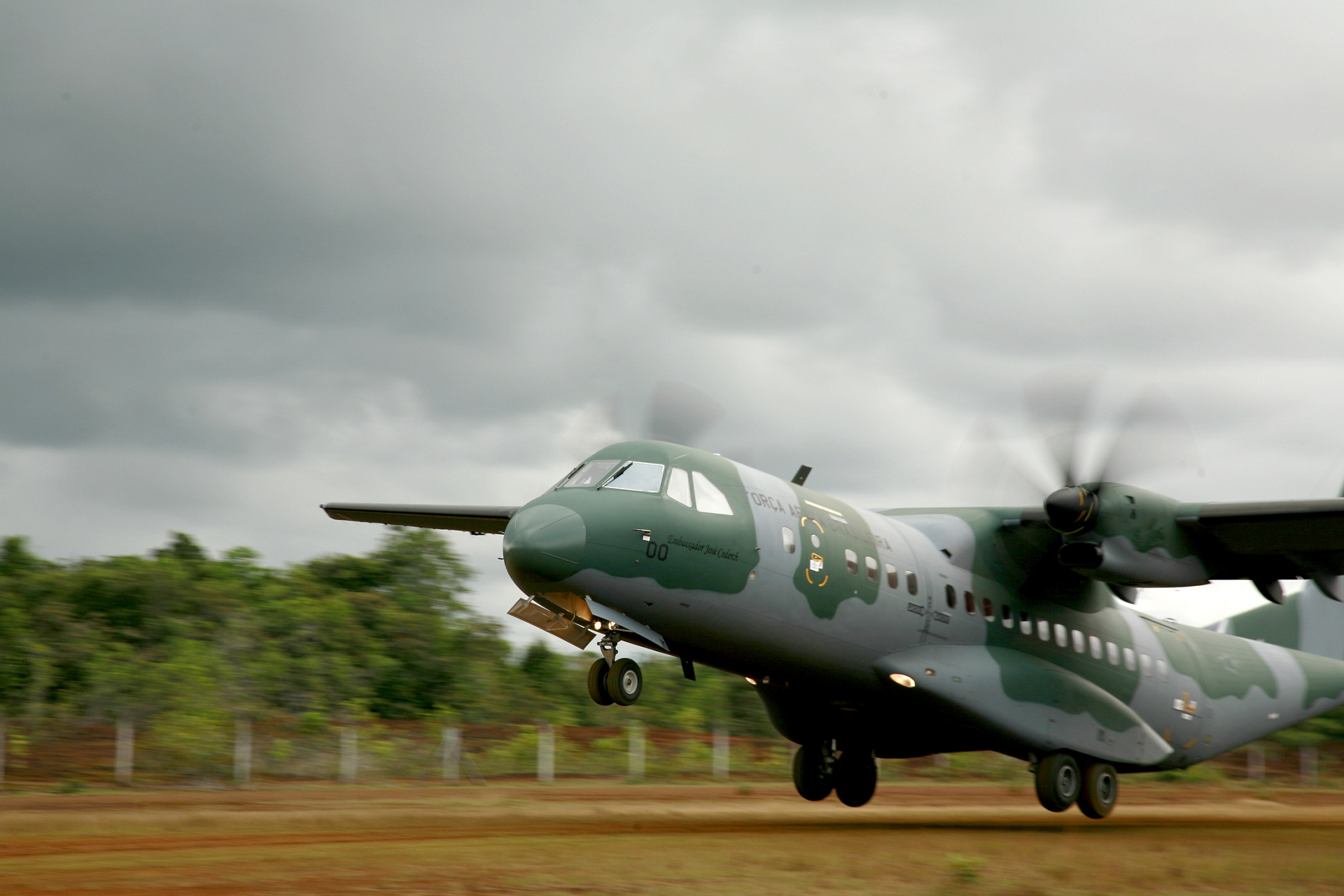 A C295 transport aircraft takes off from a semi-prepared airstrip.