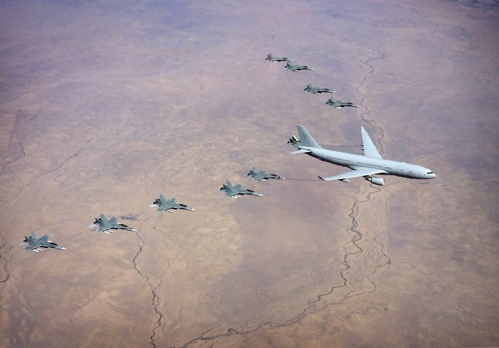 Ten No. 3 Squadron F/A-18A/B Hornets fly in a formation over the Northern Territory, while a No. 33 Squadron KC-30A Multi-Role Tanker Transport refuels two of the aircraft.