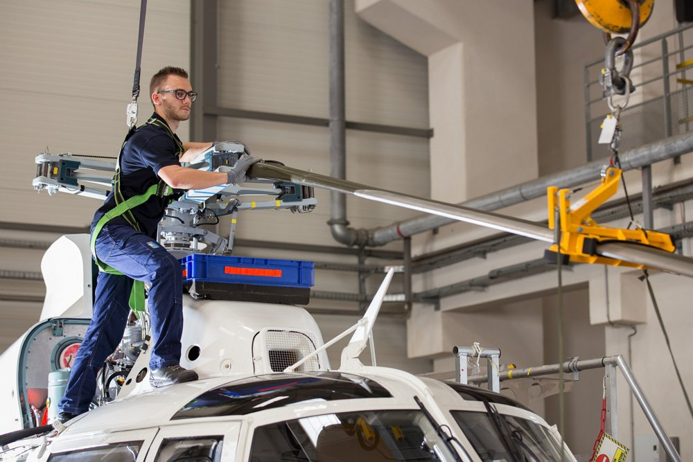 Rotor blade maintenance is performed on an Airbus AS365 N3+ helicopter.