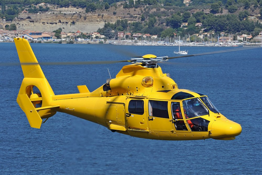Side view of an Airbus AS365 N3+ helicopter flying over water.