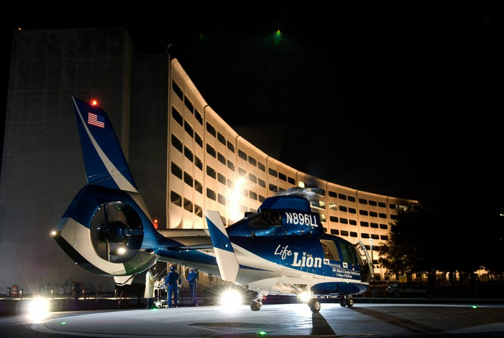 A PennState Health Life Lion AS365 N3+ used for helicopter emergency medical service (HEMS) on a helipad at night.