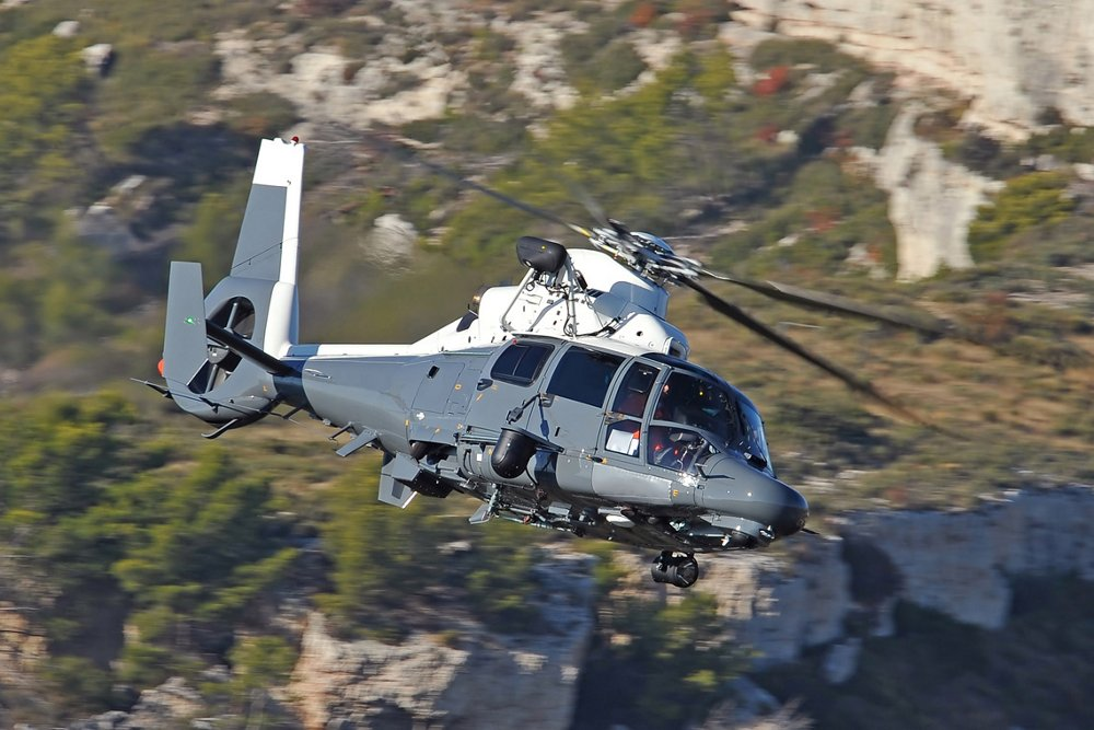 Side view of an Airbus AS565 MBe military helicopter banking over mountainous terrain.
