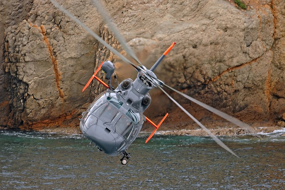 An Airbus AS565 MBe military helicopter flies over water.