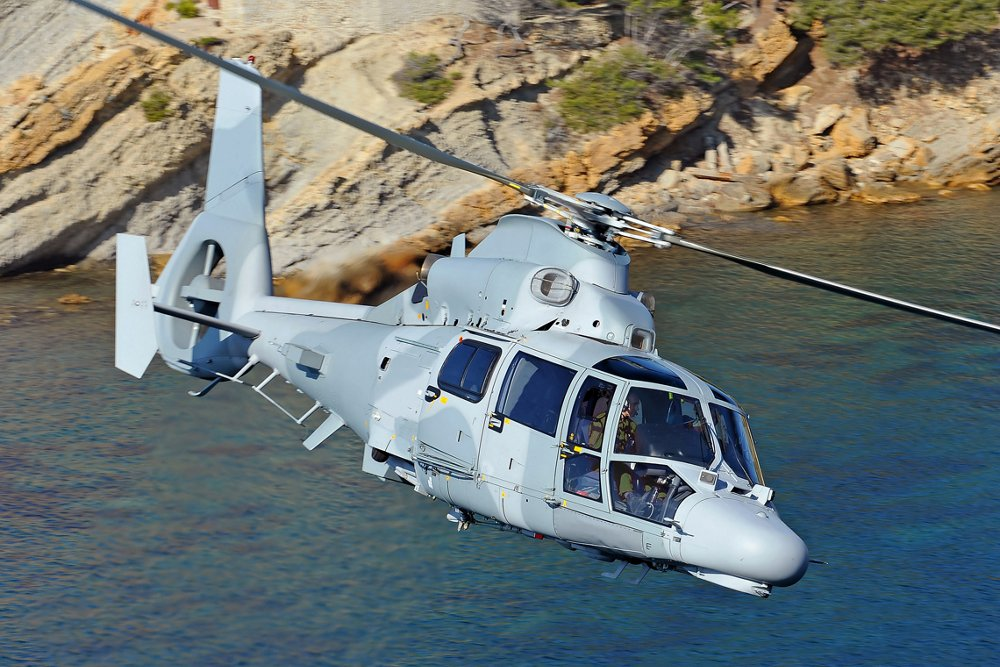 Side view of an Airbus AS565 MBe military helicopter flying over coastal terrain.
