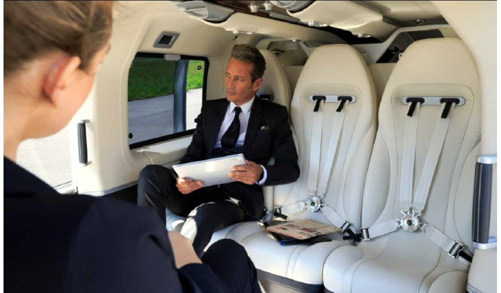 Two business professionals sit in an Airbus Corporate Helicopters cabin.