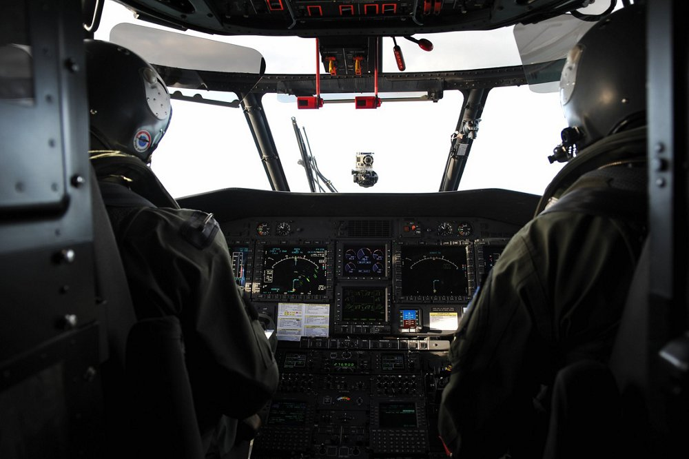 "An ""over the shoulder"" photo of pilots inside the cockpit of an Airbus H225M military helicopter."