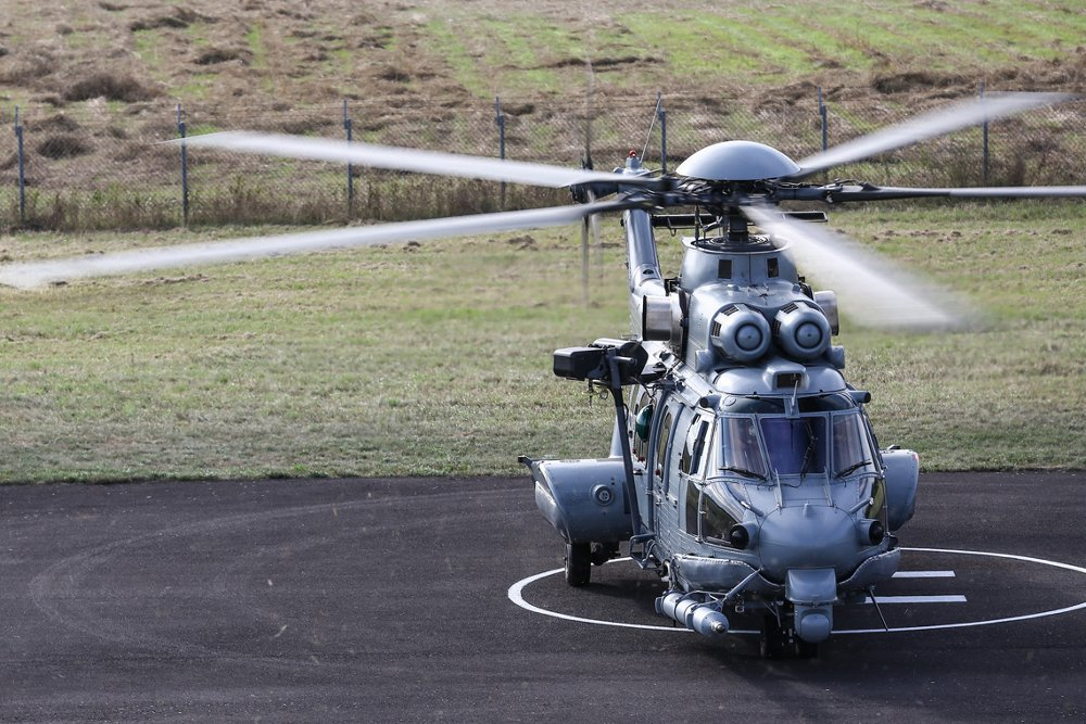 An Airbus H225M military helicopter is shown on a helipad with its main and tail rotor systems turning.