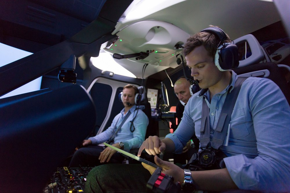 A helicopter pilot reviews digital documentation on a tablet device inside the cockpit.