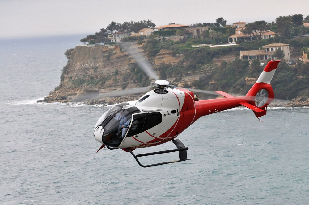 Side view of an Airbus H120 helicopter flying over water.