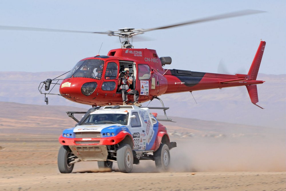 An Airbus H125 helicopter flies low to film an off-road race.