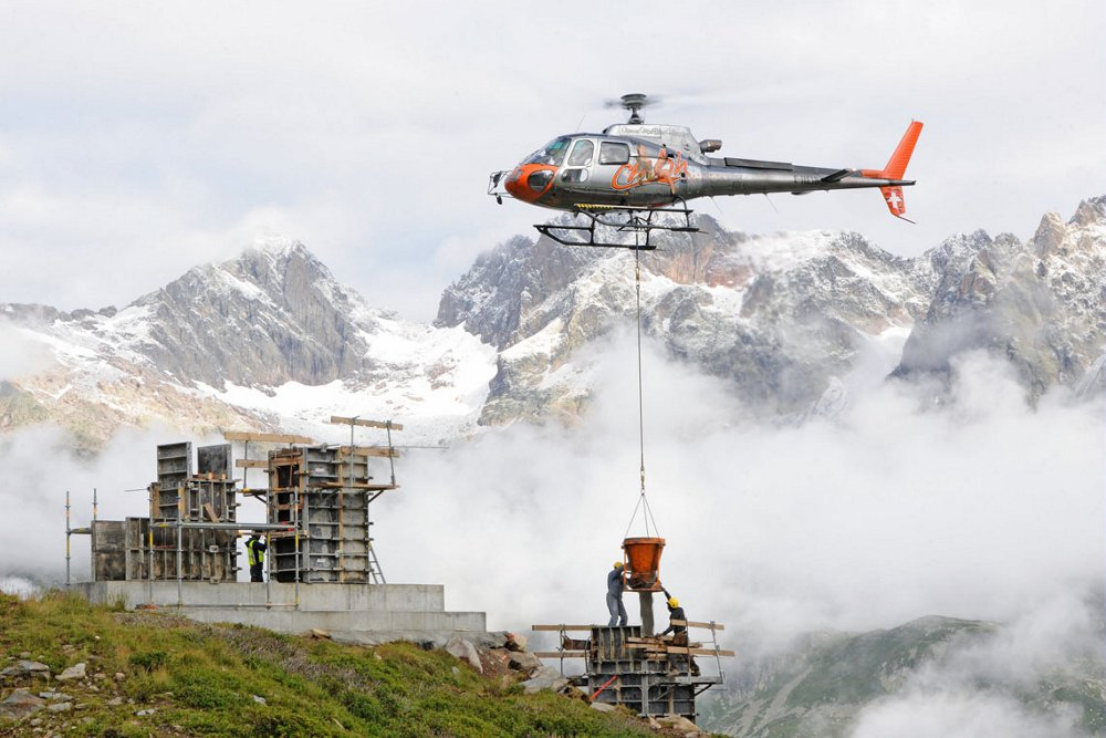 An Airbus H125 helicopter performs aerial work duties in a mountainous area.