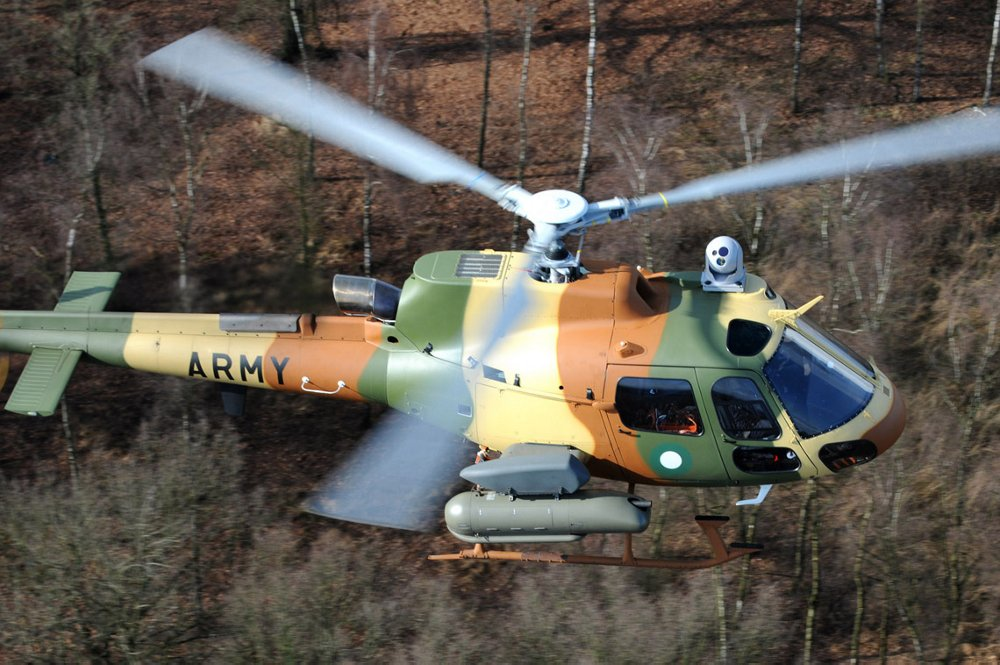 Aerial view of an H125M military helicopter flying over a wooded area.