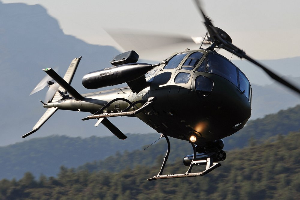 An in-flight Airbus H125M military helicopter is operated in mountainous terrain.