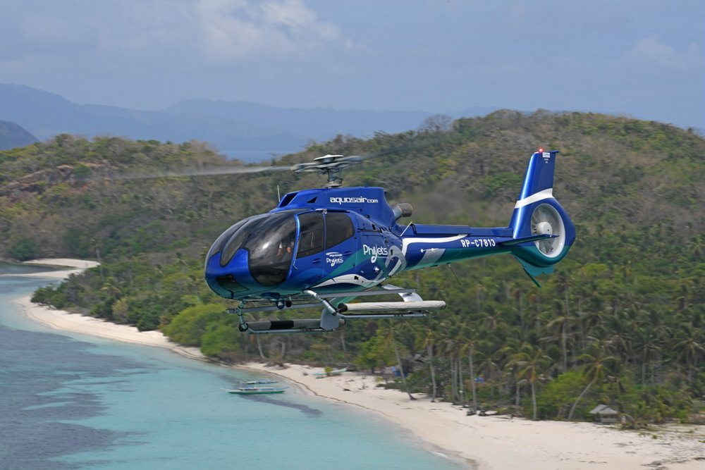 A Philjets-operated H130 helicopter flies over a picturesque beach setting
