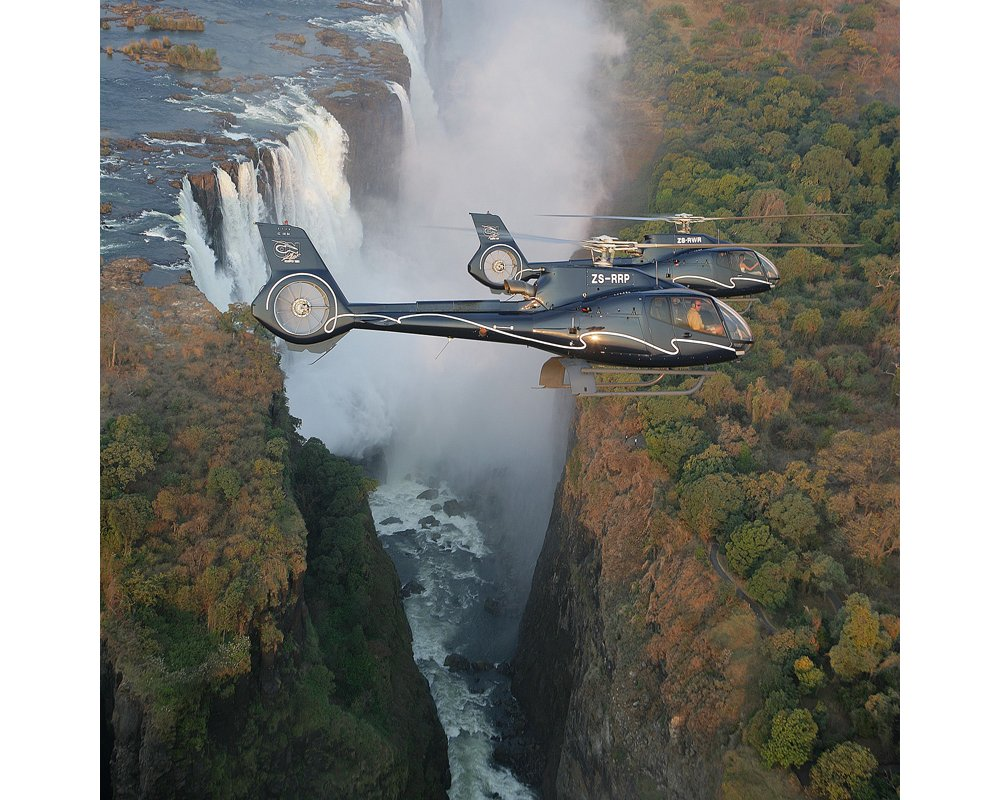 Two Airbus H130 helicopters fly in formation near a waterfall.