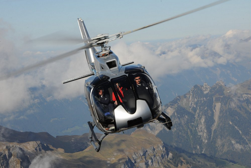 Head-on view of an in-flight Airbus H130 helicopter operating above mountainous terrain.