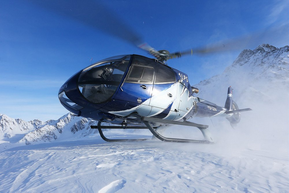 An Airbus H130 helicopter touches down to land in snowy, mountainous conditions