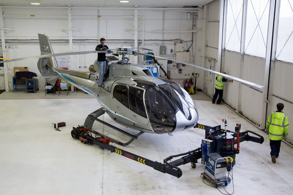 An Airbus H130 helicopter undergoes maintenance checks in a hangar