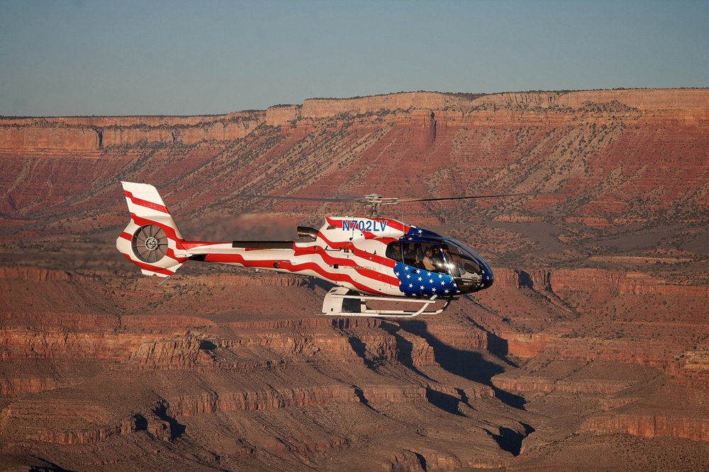 An H130 helicopter with distinctive U.S. flag livery flies over the Grand Canyon
