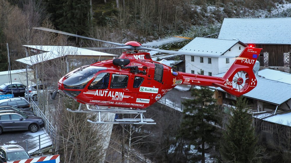 An Airbus H135 helicopter operated by Aiut Alpin Dolomites for rescue missions flies in a residential area