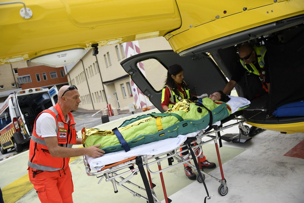 A patient is loaded onto an Airbus H135 helicopter configured for emergency medical service (EMS) missions.