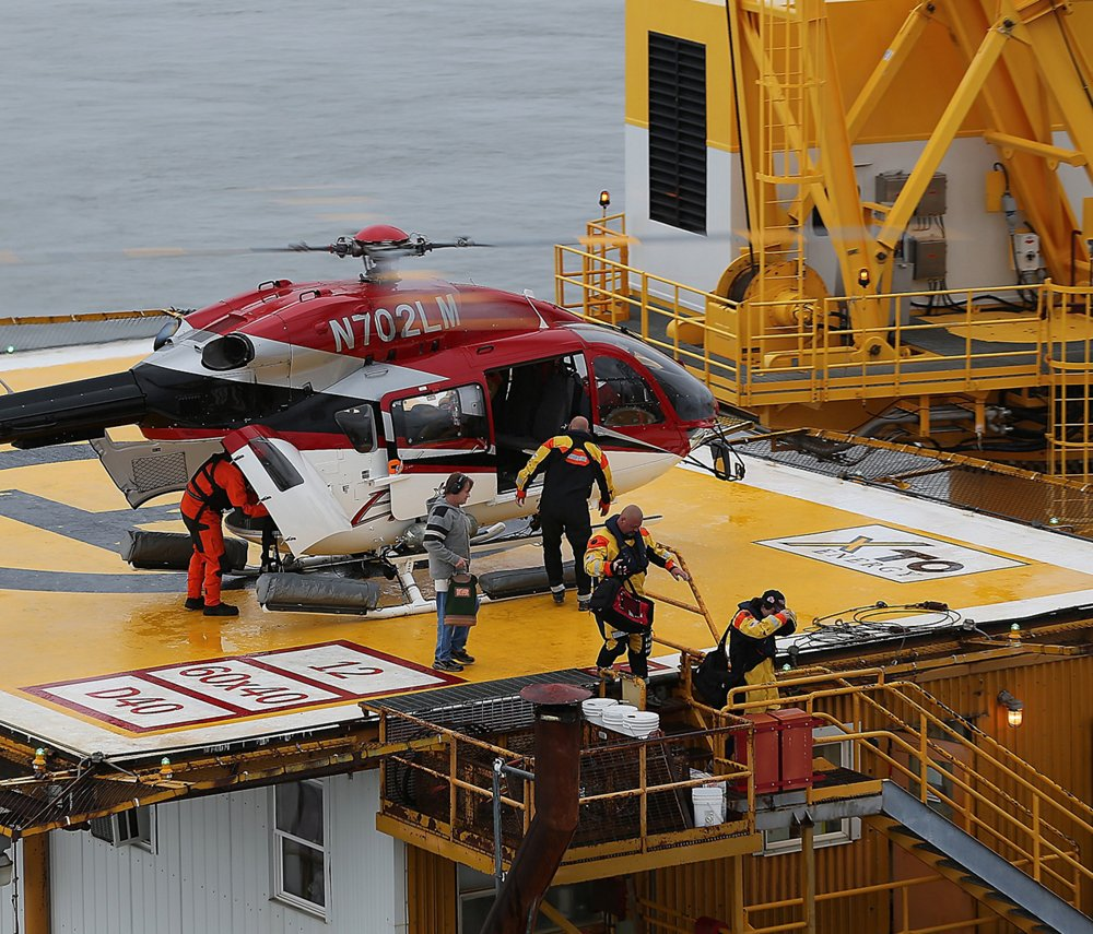 Oil and gas workers disembark from an Airbus H145 helicopter equipped with an offshore mission equipment package