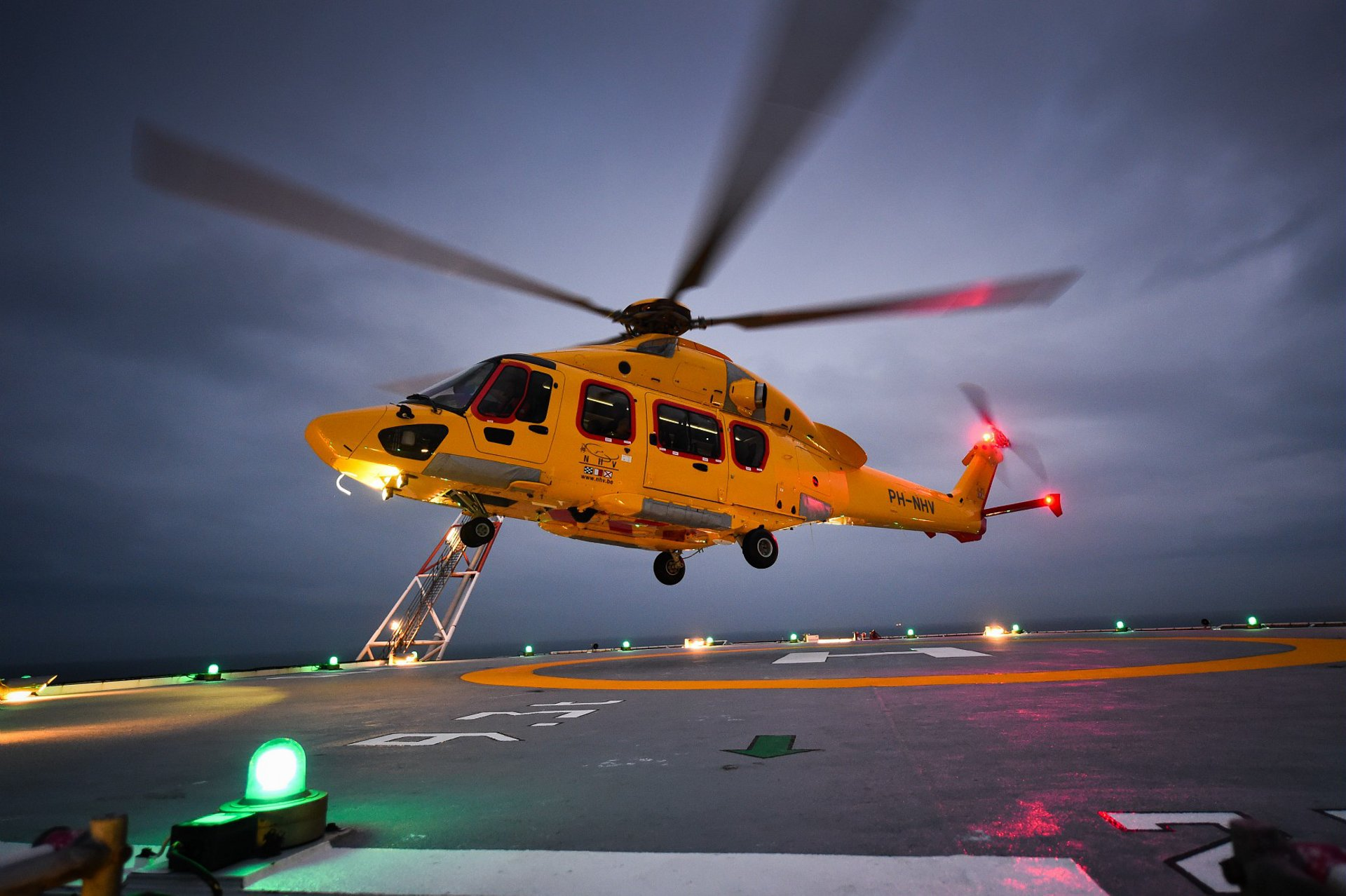 An Airbus H175 helicopter hovers over a helipad with dark skies above.