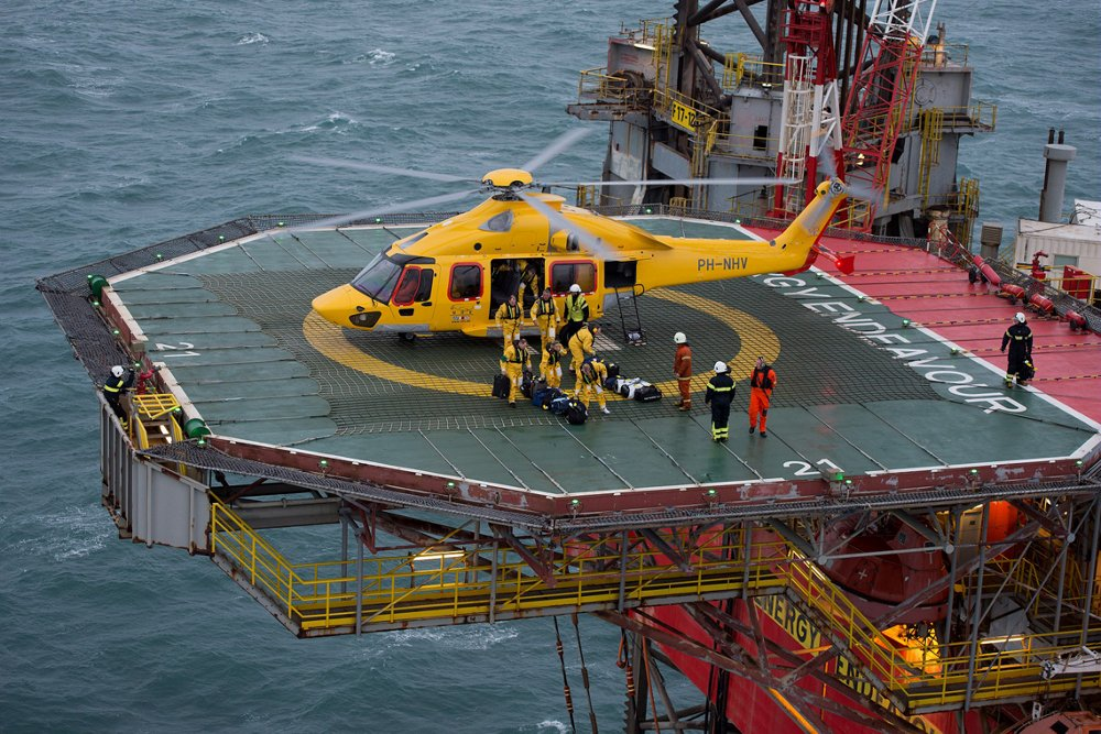 An Airbus H175 helicopter is shown on a helipad with oil and gas workers nearby.