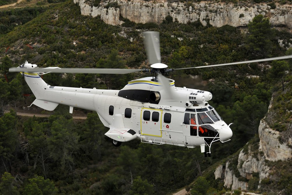 Side view of an in-flight Airbus H215 helicopter.