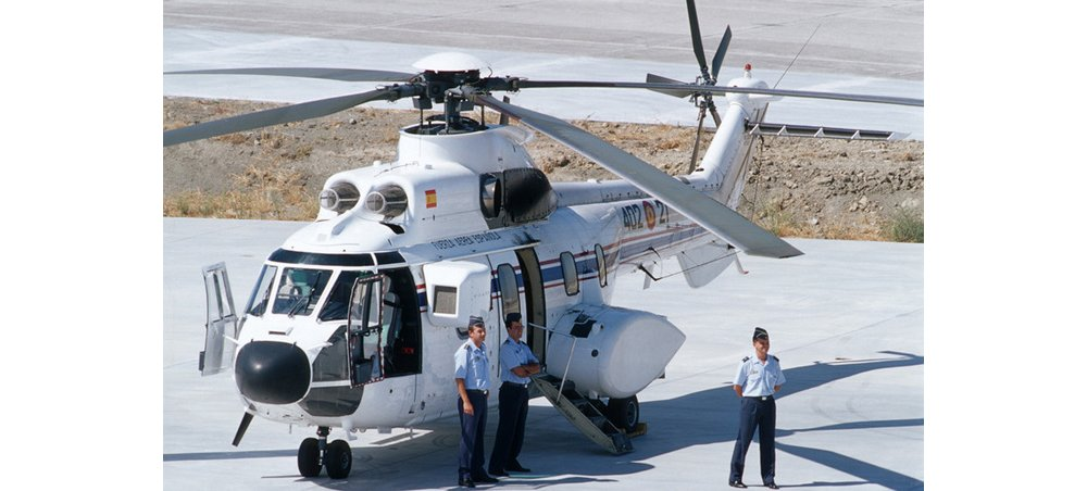 An Airbus H215 helicopter configured for passenger transport is shown parked on a helipad.