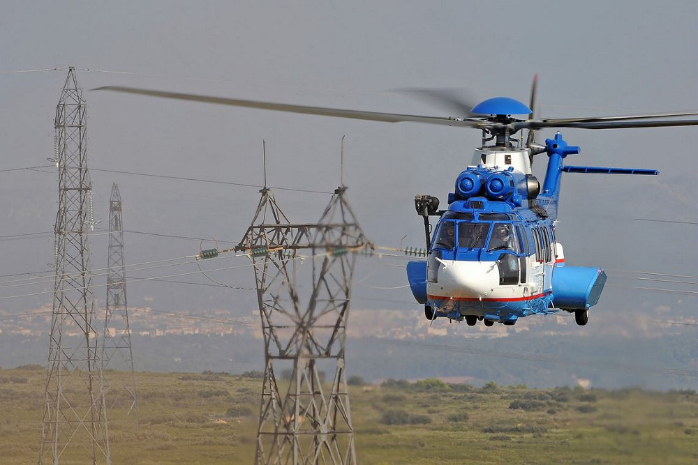 Head-on view of an in-flight Airbus H225 helicopter with power lines in the background.