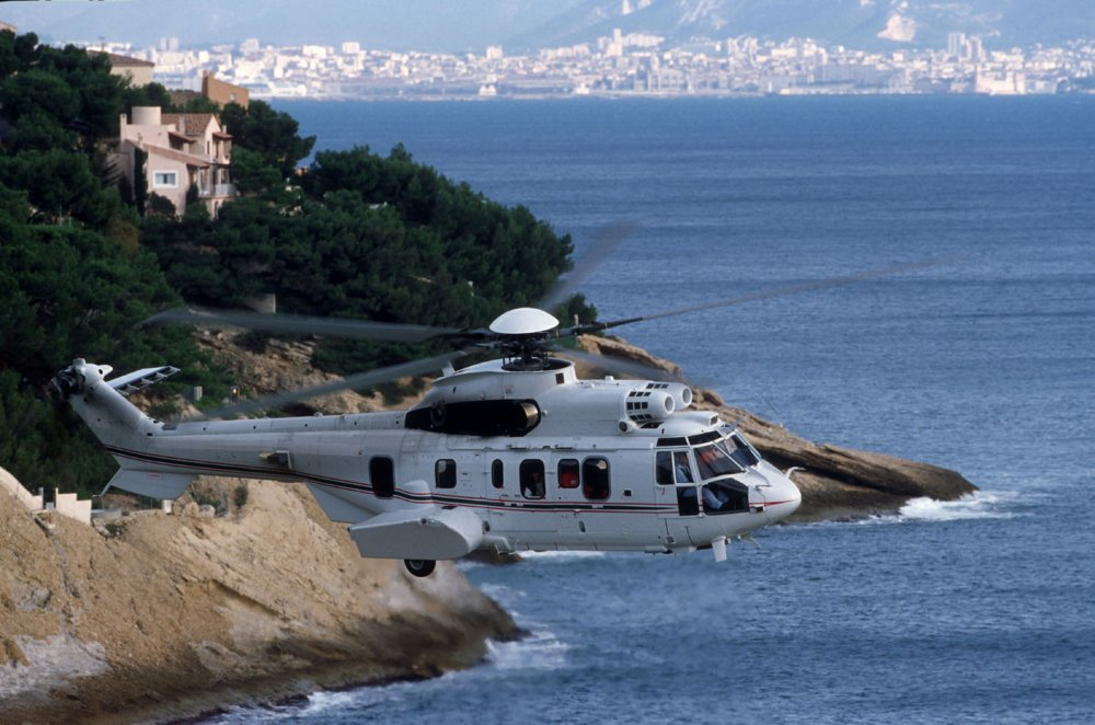 An Airbus H225 helicopter configured for VIP transport flies over a coastal area.