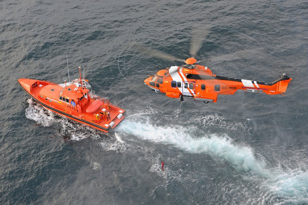 An aerial photo of an in-flight Airbus H225 helicopter configured for search and rescue (SAR) operations.