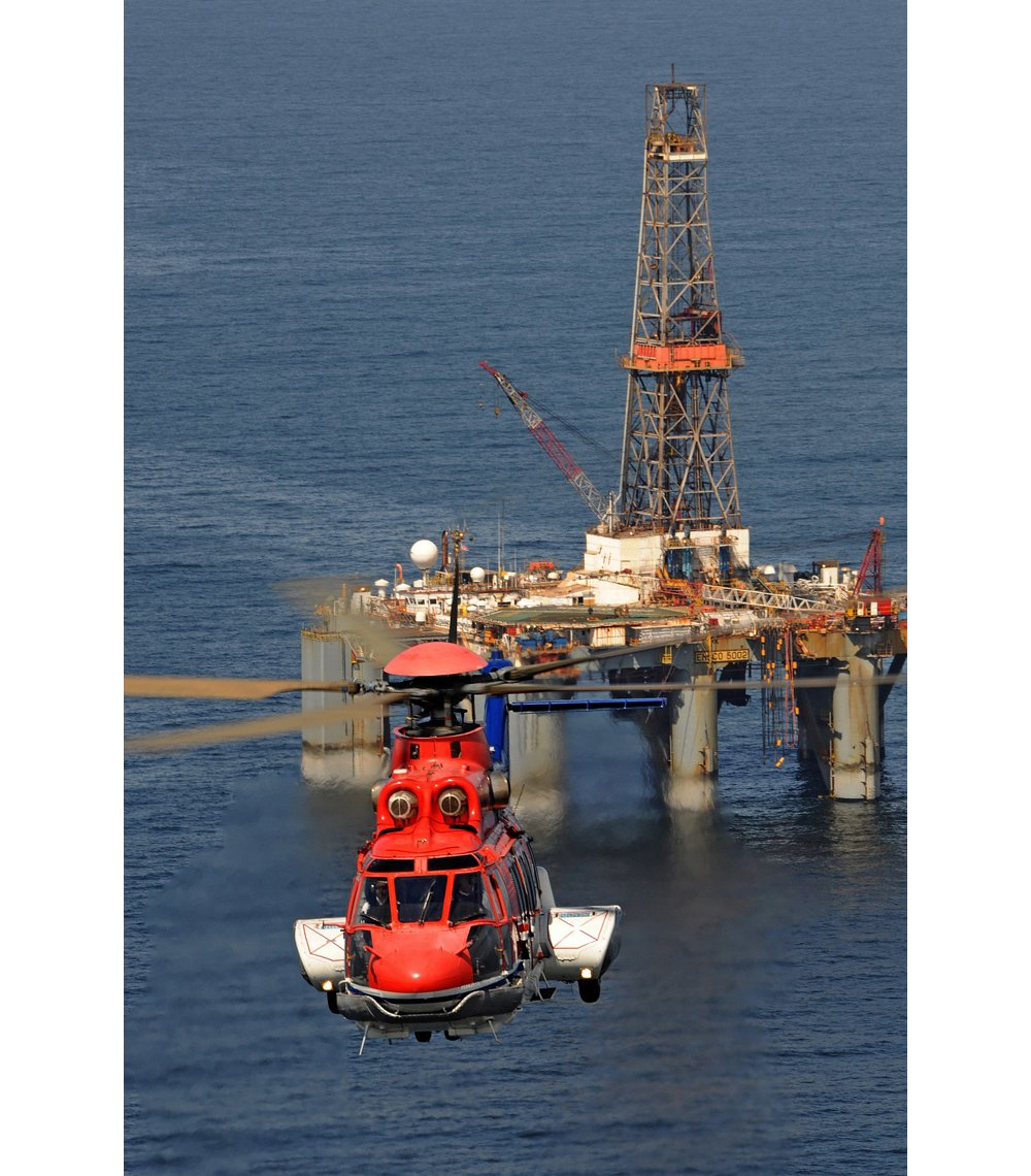 Head-on photo of an Airbus H225 helicopter flying away from an offshore oil and gas platform.
