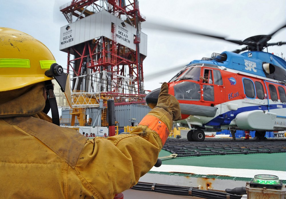 An oil and gas worker signals the pilot inside an Airbus H225 helicopter.