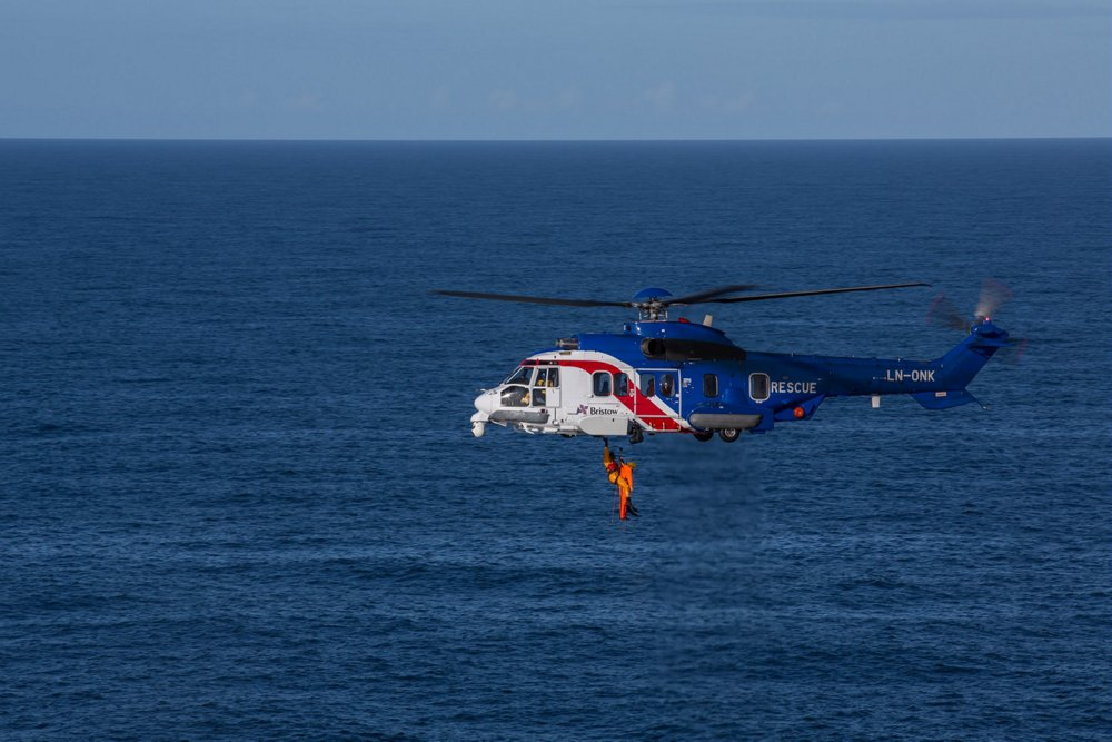 Side view of an Airbus H225 helicopter flying over a body of water.
