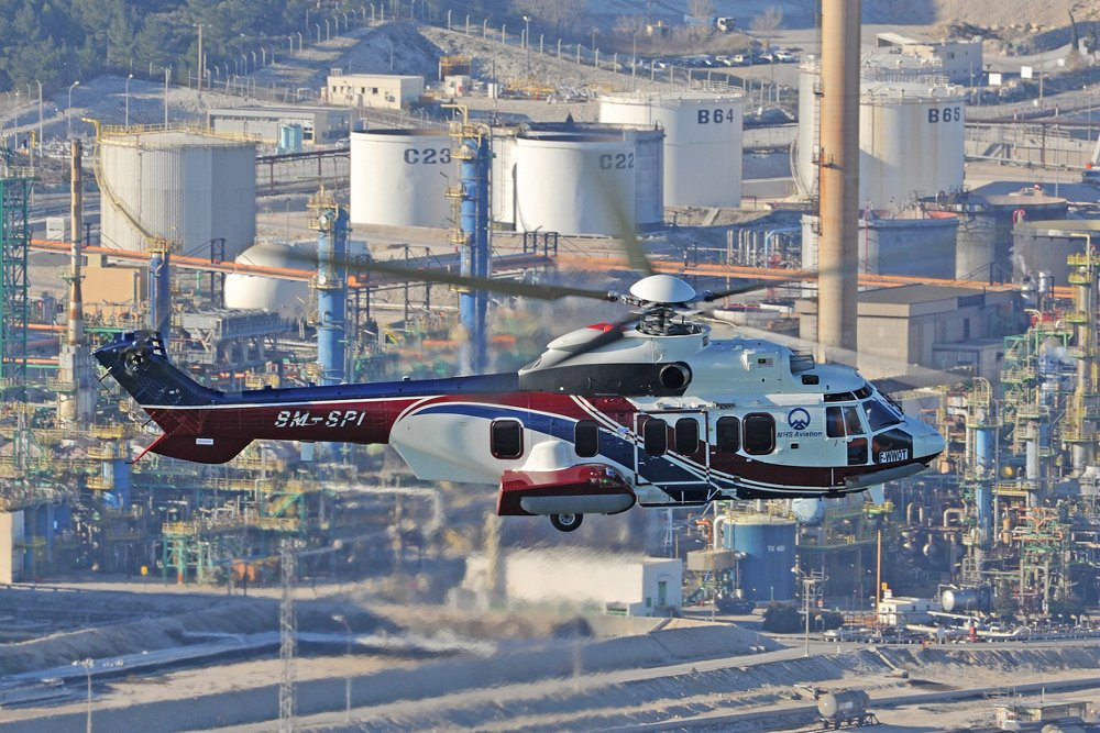 Side view of an Airbus H225 helicopter performing an oil and gas pipeline surveillance mission.
