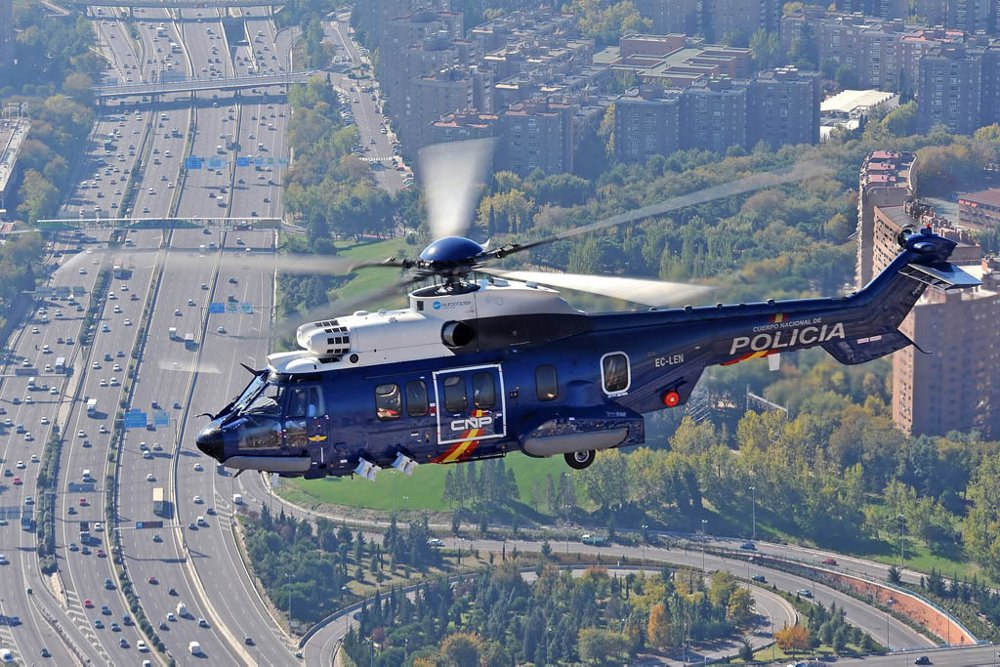 An Airbus H225 helicopter equipped for public service missions flies over a busy highway.