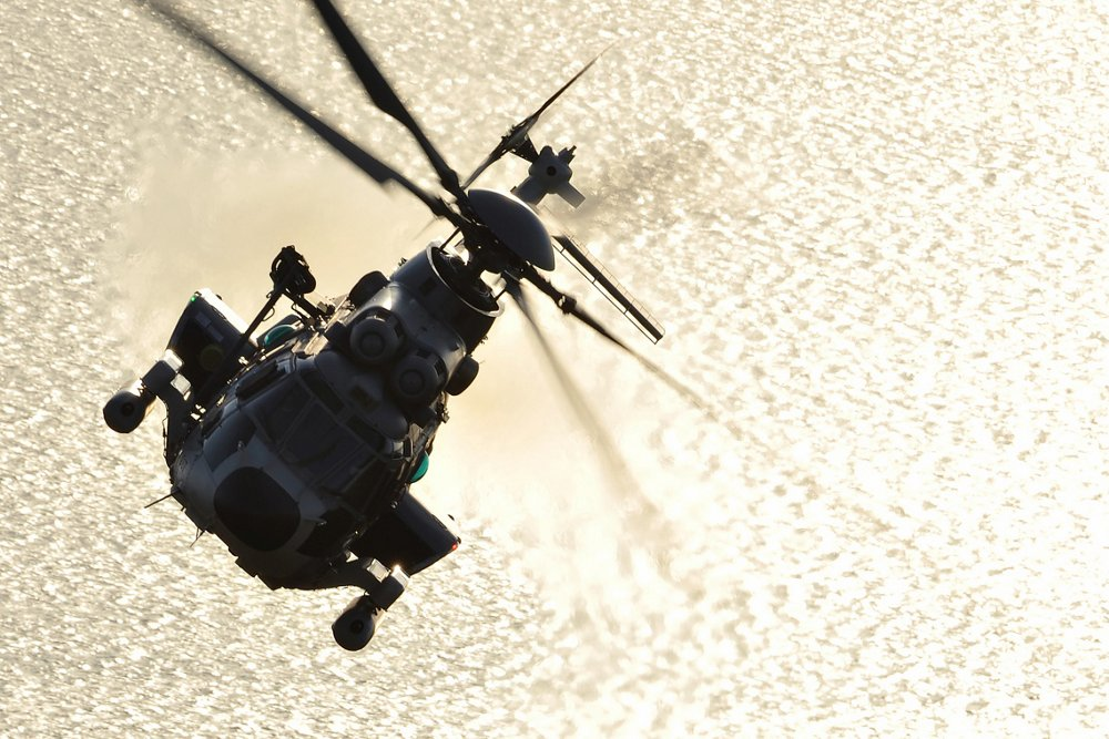 Head-on photo of an Airbus H225M military helicopter banking over water.