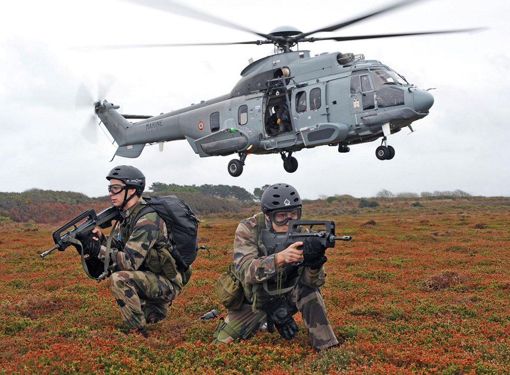 An Airbus H225M military helicopter takes off with two crouching soldiers shown in the foreground.